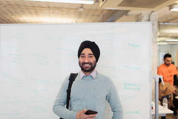 Portrait smiling, confident Indian businessman in turban standing at whiteboard in office Wall mural
