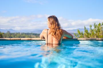 Serene woman in sunny swimming pool