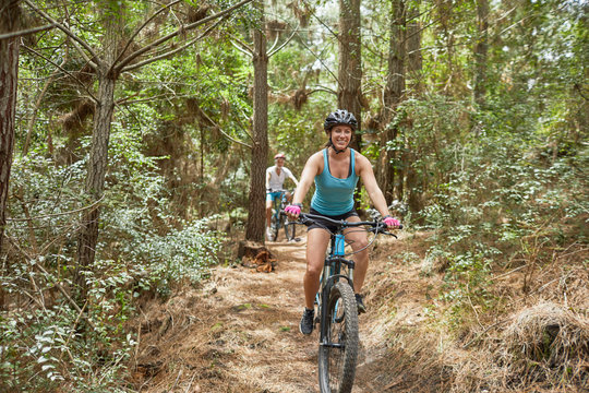 Carefree woman mountain biking on trail in woods
