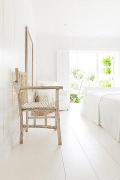 Simple wood armchair in white beach house bedroom