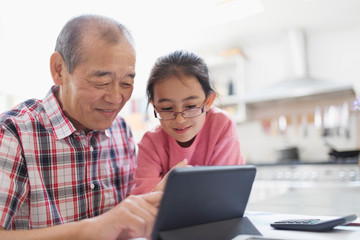 Grandfather and granddaughter using digital tablet Fotomurales