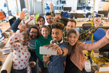 Enthusiastic creative business team cheering, taking selfie in office