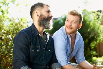 Male gay couple talking in garden