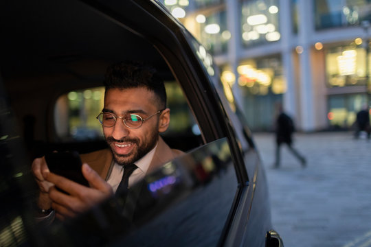 Businessman using smart phone in crowdsourced taxi at night