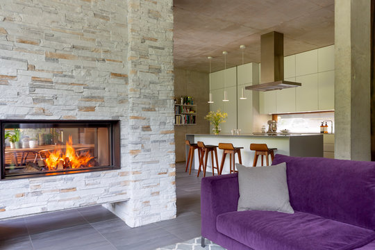 Modern living room with brick fireplace open to kitchen