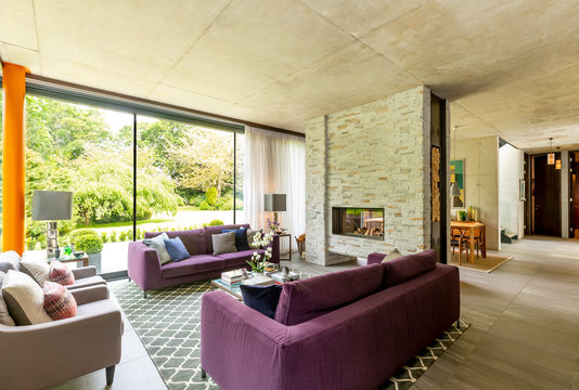 Modern living room with brick fireplace and view of garden