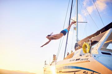Young man diving off catamaran