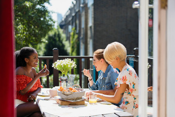 Young women friends eating brunch on sunny apartment balcony