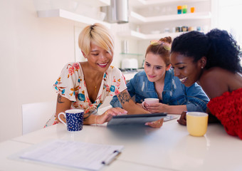 Young women friends drinking coffee using digital tablet at kitchen table Wall mural