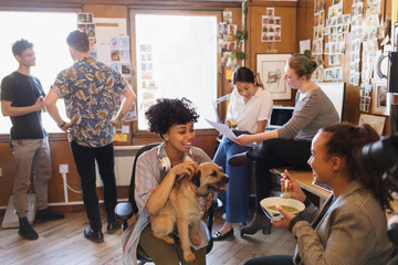 Creative business people with dog working and eating in office
