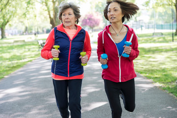 Active senior women friends jogging with hand weights in park