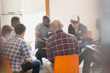Men reading and discussing bible in circle in prayer group