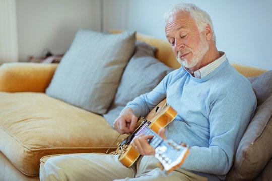 Active senior man playing guitar on living room sofa