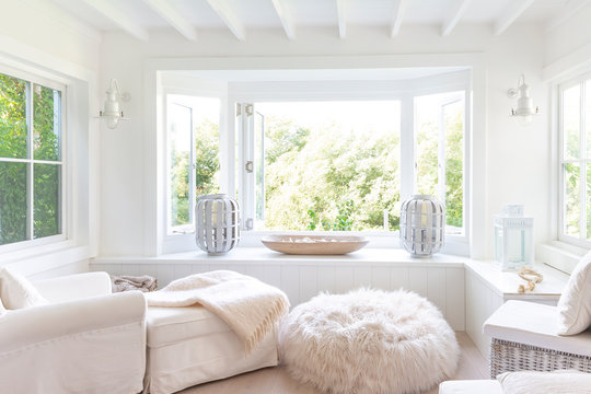 White home showcase sitting area with windows open to garden