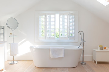Tranquil white home showcase bathroom with soaking tub
