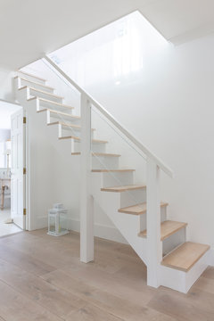 Simple white and wood stairs in home showcase foyer