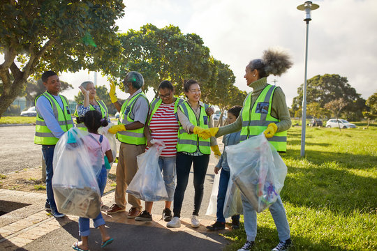 Happy volunteers celebrating, cleaning litter from sunny park