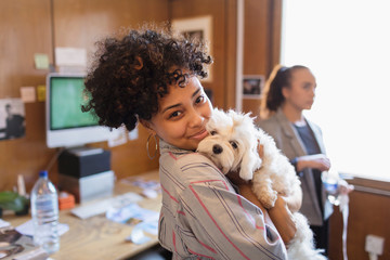 Portrait smiling creative businesswoman with cute dog in office