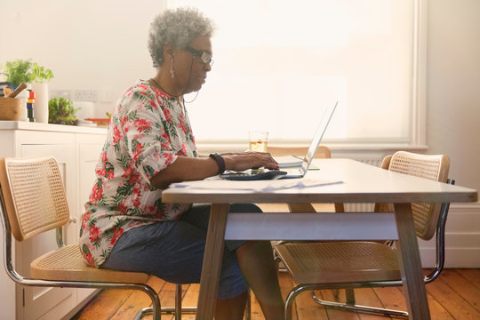 Senior woman paying bills at laptop in kitchen