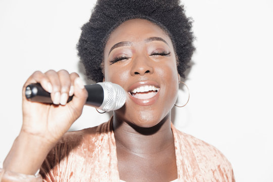 Young woman with microphone singing