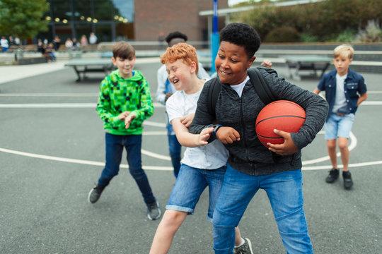 Tween boys playing basketball in schoolyard