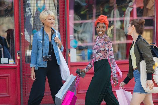 Young women friends shopping, walking on urban sidewalk