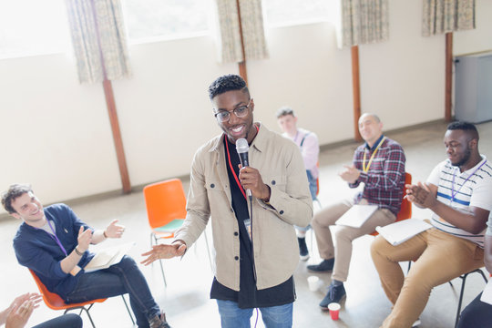 Man with microphone leading group therapy