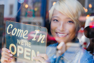 Portrait confident young female shop owner holding Open sign at window