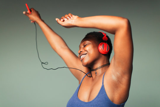 Carefree young woman with headphones and mp3 player dancing