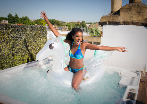 Playful, exuberant young woman in bikini sitting n inflatable pegasus in rooftop hot tub
