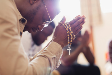 Man praying with rosary in prayer group
