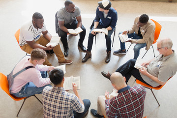 Men reading and discussing bible in prayer group circle