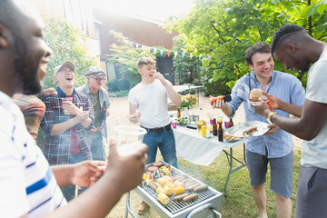 Male friends laughing and eating around barbecue grill in backyard