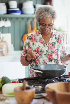 Active senior woman cooking at stove in kitchen