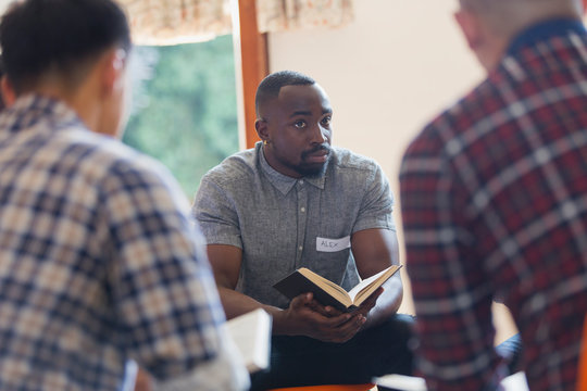 Attentive young man with bible in prayer group