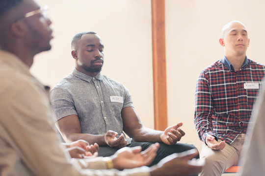 Men praying with eyes closed in prayer group