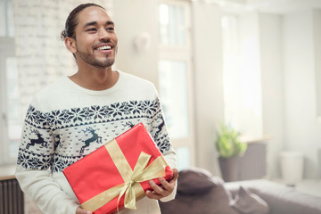 Young man in Christmas sweater holding gift