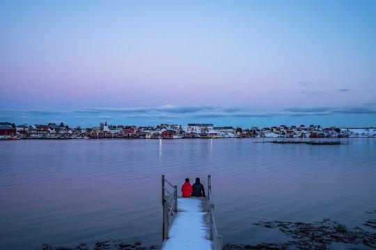 Couple sitting at the edge of snowy pier overlooking waterfront fishing village, Reine, Lofoten Islands, Norway