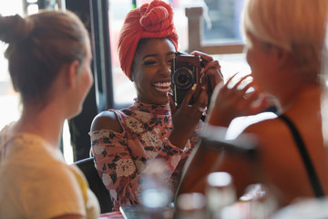 Young woman photographing friend with digital camera in cafe