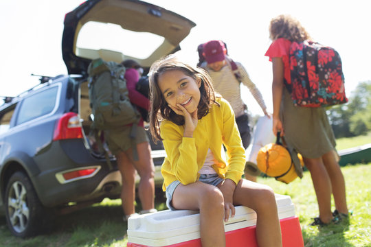 Portrait smiling girl camping with family, unloading car