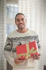 Portrait smiling young man in Christmas sweater holding gift