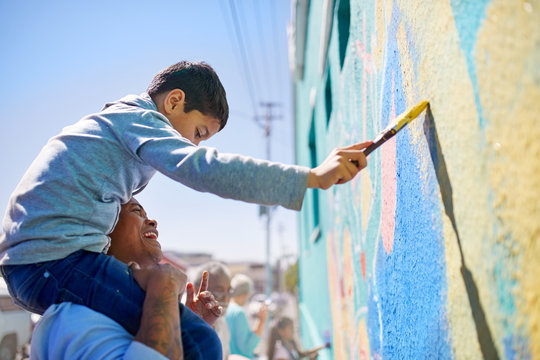 Father and son volunteers painting mural on sunny wall