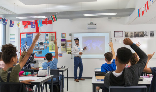 Junior high school students raising hands for teacher leading lesson in classroom
