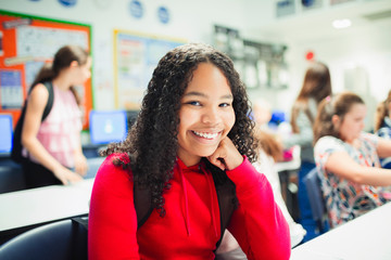 Portrait smiling, confident junior high school girl in classroom