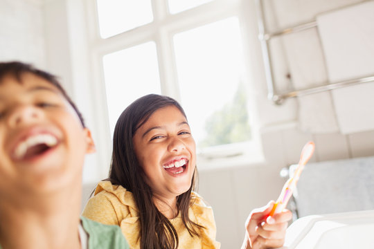 Portrait laughing brother and sister brushing teeth in bathroom