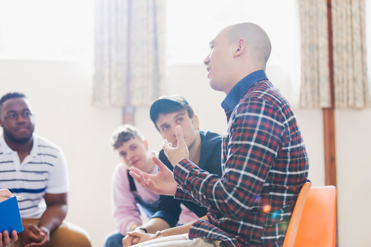 Men talking and listening in group therapy