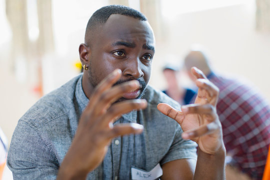 Serious young man talking, gesturing in group therapy