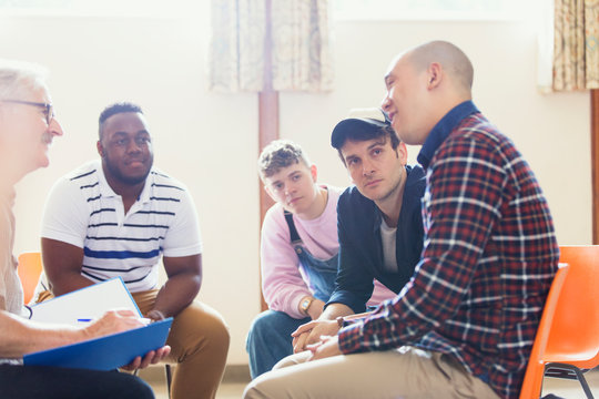 Attentive men talking and listening in group therapy