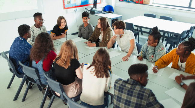 High school students talking at table in debate class