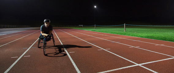 Portrait confident, determined young female paraplegic athlete training for wheelchair race on sports track at night